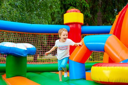 happy excited boy having fun on inflatable attraction playground Stockfoto