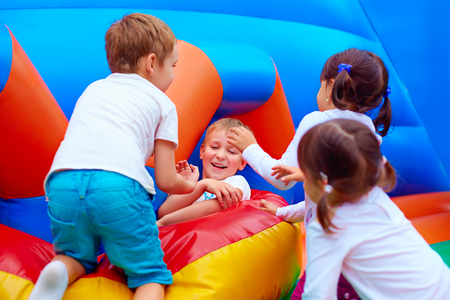 children playground: excited kids having fun on inflatable attraction playground Stock Photo