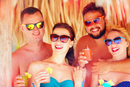 all smiles: group of happy friends having fun on tropical beach, holiday party