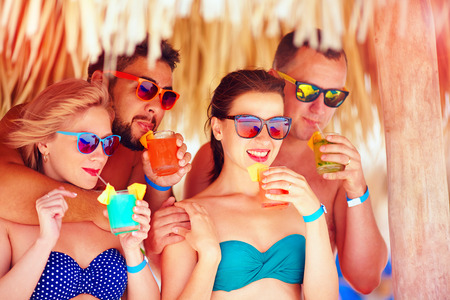 all smiles: group of happy friends having fun on tropical beach, drinking colorful cocktails Stock Photo