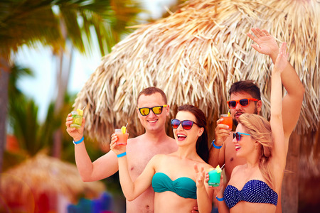 all smiles: group of happy friends having fun on tropical beach, summer holiday party