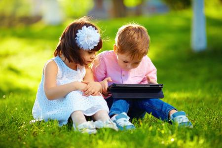 multy: two cute kids using digital tablet in summer garden