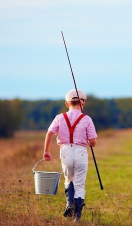 pecheur: vue arrière d'enfant mignon marchant pour la pêche
