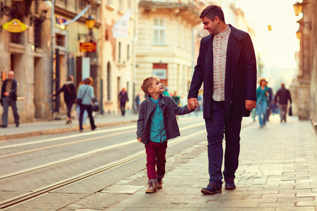 talking: fashionable father and son walking in old city street