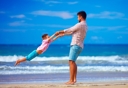playful: happy excited father and son playing on summer beach, enjoy life