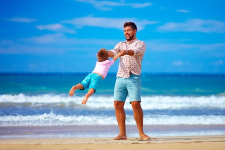 excited man: happy excited father and son playing on summer beach, enjoy life