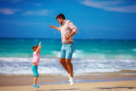 child sport: happy excited father and son jumping on summer beach, enjoy life