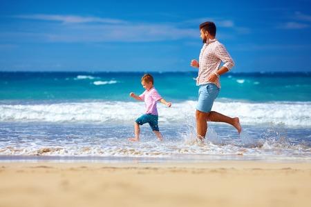 padres: padre excitado feliz e hijo que se ejecutan en la playa de verano, disfrutar de la vida