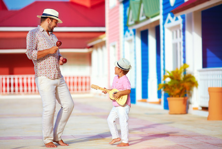 street life: happy family playing music and dancing on caribbean street
