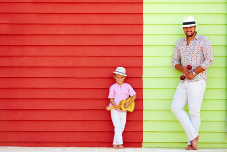 street life: happy father and son with musical instruments near the colorful wall Stock Photo