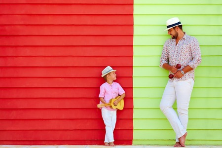 happy father and son with musical instruments near the colorful wall 스톡 콘텐츠