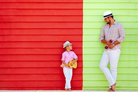 instrumentos musicales: feliz padre e hijo con instrumentos musicales cerca de la pared de colores Foto de archivo