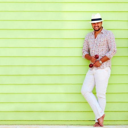 man shirt: happy man with maraca playing music near the colorful wall