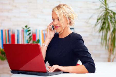 사무실에서 전화 얘기하고 매력적인 비즈니스 여자