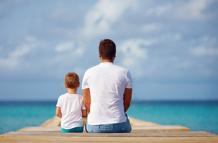 convivencia familiar: padre e hijo sentados en el muelle cerca del mar Foto de archivo