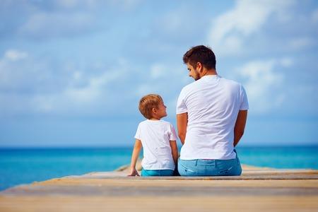 dos personas hablando: padre e hijo sentados en el muelle y hablar
