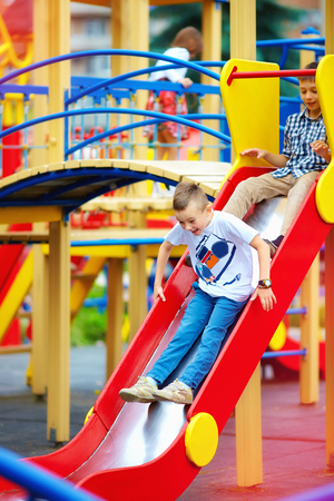 school activities: group of happy kids sliding on colorful playground