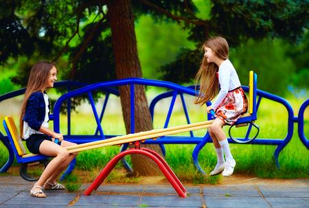かわいい女の子の遊び場でシーソー上で楽しんで