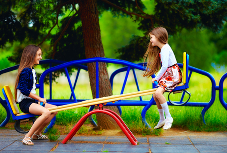 cute girls having fun on seesaw at playground Banco de Imagens