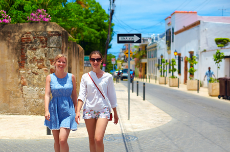 dominican: happy young girls, tourists walking on streets in city tour, Santo Domingo Stock Photo