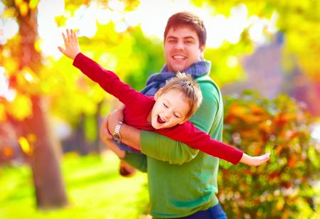 一起使用在秋天公园的愉快的父亲和儿子