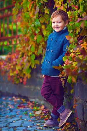 niño modelo: muchacho sonriente lindo que presenta cerca de la pared de colores Foto de archivo