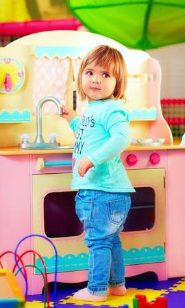 juguete: linda niña jugando con cocina de juguete en el jardín infantil Foto de archivo