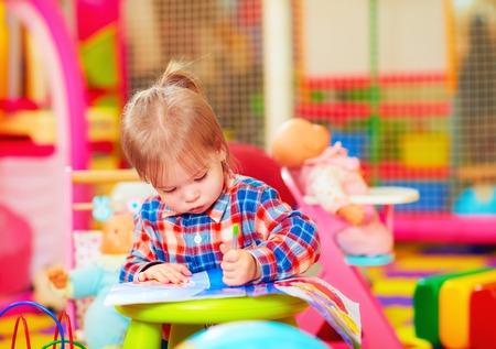 kinder: Linda niña dibujar con el lápiz en el jardín de infantes