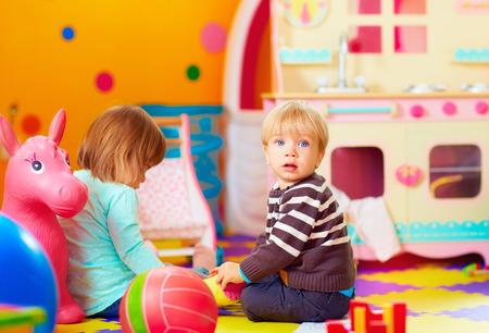 play: lindos niños pequeños que juegan juntos en guardería