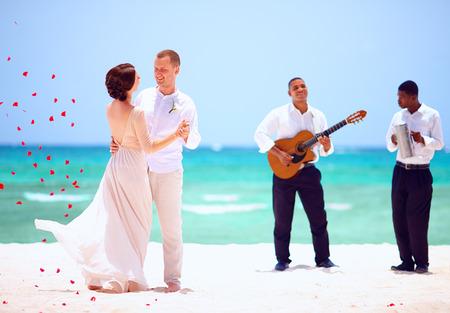 美しいトロピカルなビーチ、生演奏で踊る新郎新婦 写真素材
