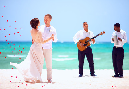 beautiful bride and groom dancing on tropical beach, live music Stock Photo