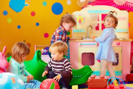 Ragazzini svegli che giocano con i giocattoli in vivaio gruppo di scuola materna Archivio Fotografico - 47972333