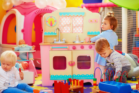 daycare: cute little kids playing with toys in nursery group of kindergarten Stock Photo