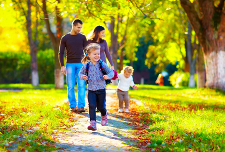 and activities: happy young girl running in autumn park with her family on background