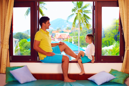 tropics: happy father and son having fun, sitting on windowsill during vacation in tropics