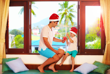 tropics: father presenting son a tasty candies on christmas, while sitting on windowsill in tropics