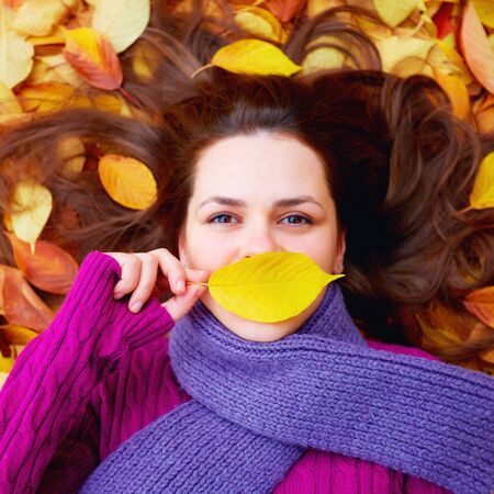 view girl: young girl lying among autumn leaves, hiding lips behind a leaf
