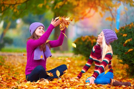 colo: pretty girls, friends having fun in colorful autumn park, tossing the leaves up Stock Photo