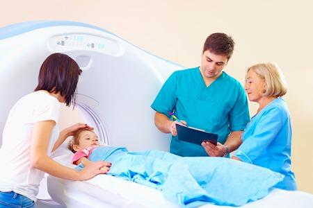jonge moeder kalmerende baby voor de medische procedure in ct-scanner