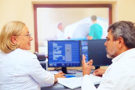 mri: medical staff discussing mri results during procedure Stock Photo