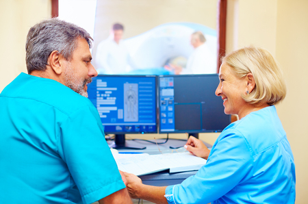 tomography: experienced adult medical stuff talking about patient diagnosis in tomography room Stock Photo
