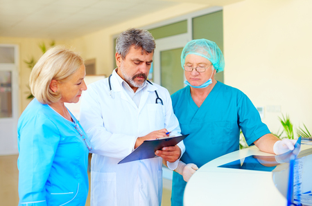 indices: experienced doctor and medical staff consulting about health record in hospital