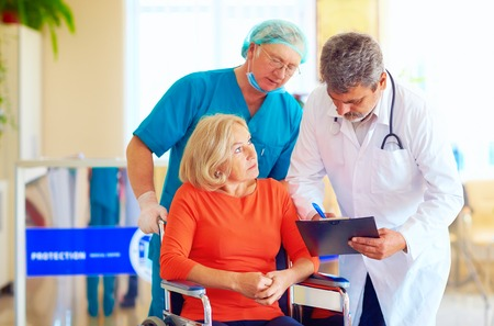 mature female patient on wheelchair listens to doctor prescription medication
