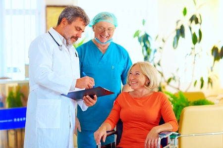 medico con paciente: feliz médico y cirujano de consultoría paciente sobre el tratamiento antes de la descarga del hospital