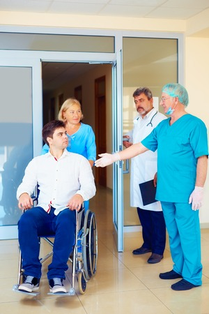 discharge: surgeon and medical staff talking with young adult man in wheelchair, in hospital Stock Photo