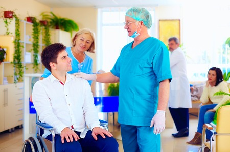 surgeon and medical staff talking with young adult man in wheelchair, in hospital Stok Fotoğraf
