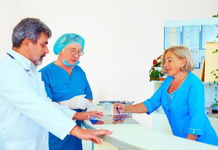 indices: medical staff consulting about health record at hospital desk
