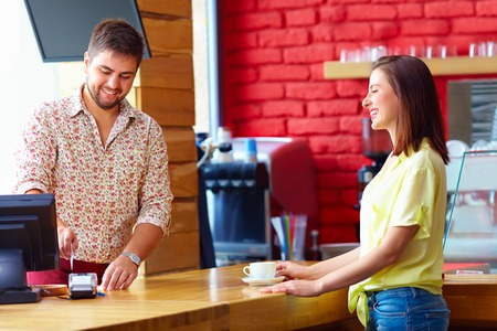 cashier serves customer at the cash desk in cafe Stock Photo