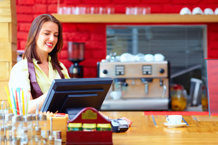 young female cashier operating at the cash desk in cafe Foto de archivo