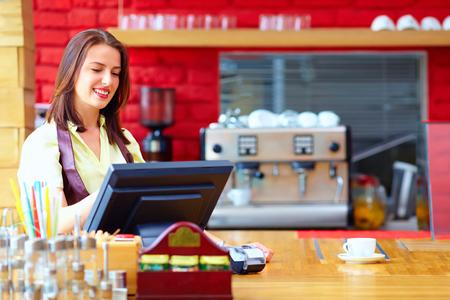 jonge vrouwelijke kassier werken aan de kassa in cafe